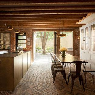 Bild på ett rustikt brun brunt kök, med luckor med glaspanel, vita skåp, rostfria vitvaror, tegelgolv, en köksö, en integrerad diskho, träbänkskiva, vitt stänkskydd och rött golv