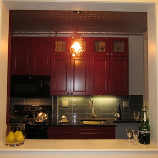 Design ideas for a small midcentury galley separate kitchen in New York with an undermount sink, raised-panel cabinets, medium wood cabinets, grey splashback, glass tile splashback, black appliances, ceramic floors, a peninsula and brown floor.