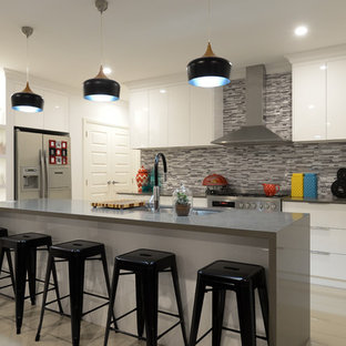 Photo of a mid-sized l-shaped kitchen in Other with a drop-in sink, flat-panel cabinets, white cabinets, multi-coloured splashback, mosaic tile splashback, stainless steel appliances, ceramic floors, beige floor, with island and grey benchtop.
