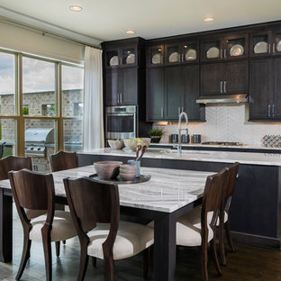 Transitional eat-in kitchen designs - Inspiration for a transitional galley medium tone wood floor and brown floor eat-in kitchen remodel in Atlanta with stainless steel appliances, an island, an undermount sink, shaker cabinets, black cabinets, white backsplash and gray countertops