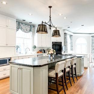 Modelo de cocina comedor tradicional con armarios con paneles con relieve, puertas de armario blancas, salpicadero blanco, electrodomésticos de acero inoxidable, suelo de madera en tonos medios, una isla y encimeras blancas