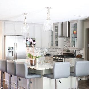 Ejemplo de cocina en L, contemporánea, pequeña, abierta, con fregadero bajoencimera, armarios con paneles lisos, puertas de armario grises, encimera de granito, salpicadero metalizado, salpicadero con mosaicos de azulejos, electrodomésticos de acero inoxidable y una isla