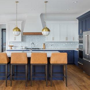 Réalisation d'une cuisine marine en L avec un évier encastré, un placard à porte shaker, des portes de placard bleues, une crédence multicolore, un électroménager en acier inoxydable, un sol en bois brun, un îlot central, un sol marron et un plan de travail blanc.