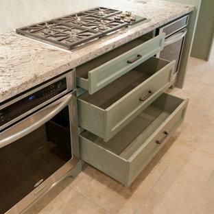 Large island style galley porcelain floor kitchen photo in Houston with a farmhouse sink, recessed-panel cabinets, green cabinets, granite countertops, white backsplash, glass tile backsplash, stainless steel appliances and an island
