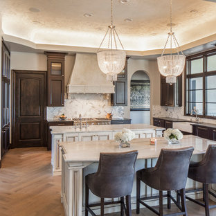 This is an example of a large victorian u-shaped separate kitchen in Austin with a farmhouse sink, beaded inset cabinets, dark wood cabinets, marble benchtops, white splashback, marble splashback, panelled appliances, medium hardwood floors, multiple islands and brown floor.