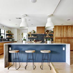 Contemporary open concept kitchen designs - Open concept kitchen - contemporary l-shaped light wood floor open concept kitchen idea in Austin with flat-panel cabinets, dark wood cabinets, blue backsplash, ceramic backsplash, paneled appliances and an island