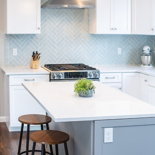 Exempel på ett avskilt, mellanstort klassiskt vit vitt u-kök, med en undermonterad diskho, skåp i shakerstil, vita skåp, bänkskiva i kvarts, blått stänkskydd, stänkskydd i keramik, rostfria vitvaror, mellanmörkt trägolv, en köksö och brunt golv
