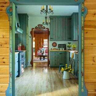 ミルウォーキーの中サイズのカントリー風おしゃれなII型キッチン (エプロンフロントシンク、フラットパネル扉のキャビネット、緑のキャビネット、木材カウンター、シルバーの調理設備の、淡色無垢フローリング、アイランドなし、茶色い床) の写真