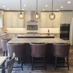 Large country l-shaped open plan kitchen in Philadelphia with an undermount sink, raised-panel cabinets, distressed cabinets, quartzite benchtops, white splashback, ceramic splashback, stainless steel appliances, porcelain floors, multiple islands, brown floor and multi-coloured benchtop.