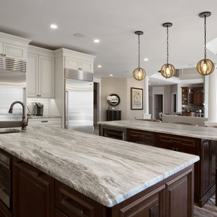 This is an example of a large country l-shaped open plan kitchen in Philadelphia with an undermount sink, raised-panel cabinets, distressed cabinets, quartzite benchtops, white splashback, ceramic splashback, stainless steel appliances, porcelain floors, multiple islands, brown floor and multi-coloured benchtop.