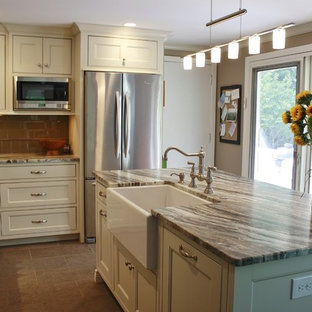 This is an example of a mid-sized transitional l-shaped eat-in kitchen in Philadelphia with a farmhouse sink, recessed-panel cabinets, white cabinets, quartzite benchtops, brown splashback, glass tile splashback, stainless steel appliances, porcelain floors and with island.