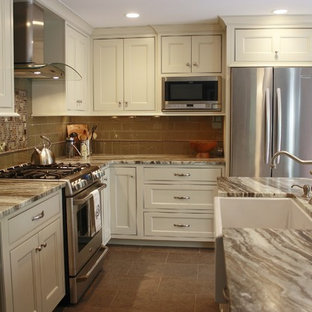 Design ideas for a mid-sized transitional l-shaped eat-in kitchen in Philadelphia with a farmhouse sink, recessed-panel cabinets, white cabinets, quartzite benchtops, brown splashback, glass tile splashback, stainless steel appliances, porcelain floors and with island.