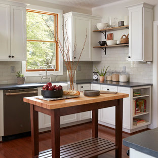 Farmhouse kitchen pictures - Kitchen - cottage l-shaped dark wood floor kitchen idea in Baltimore with a farmhouse sink, shaker cabinets, white cabinets, white backsplash, subway tile backsplash, stainless steel appliances, an island, gray countertops and soapstone countertops
