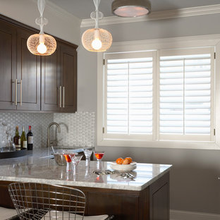 Transitional kitchen appliance - Example of a transitional l-shaped kitchen design in Minneapolis with shaker cabinets, dark wood cabinets, white backsplash and an undermount sink