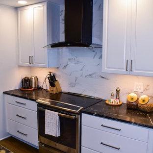 Klassisk inredning av ett mellanstort svart linjärt svart kök och matrum, med en rustik diskho, luckor med upphöjd panel, vita skåp, bänkskiva i kvarts, vitt stänkskydd, stänkskydd i porslinskakel, svarta vitvaror, mellanmörkt trägolv, en köksö och brunt golv