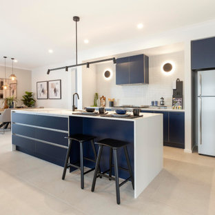Contemporary single-wall open plan kitchen in Melbourne with an undermount sink, blue cabinets, quartz benchtops, white splashback, ceramic splashback, stainless steel appliances, ceramic floors, with island, beige floor and white benchtop.