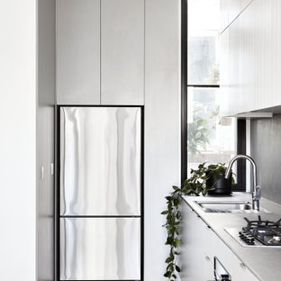 Design ideas for a mid-sized contemporary l-shaped kitchen in Melbourne with an undermount sink, flat-panel cabinets, white cabinets, grey splashback, stainless steel appliances, no island, beige floor and grey benchtop.