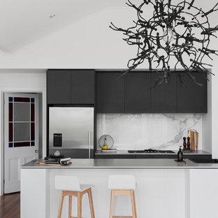 メルボルンのコンテンポラリースタイルのおしゃれなキッチン (一体型シンク、フラットパネル扉のキャビネット、黒いキャビネット、コンクリートカウンター、白いキッチンパネル、大理石のキッチンパネル、シルバーの調理設備、無垢フローリング、茶色い床) の写真