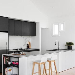 メルボルンのコンテンポラリースタイルのおしゃれなキッチン (一体型シンク、フラットパネル扉のキャビネット、黒いキャビネット、コンクリートカウンター、白いキッチンパネル、大理石のキッチンパネル、シルバーの調理設備、無垢フローリング) の写真