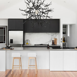 This is an example of a mid-sized contemporary galley open plan kitchen in Melbourne with an integrated sink, flat-panel cabinets, black cabinets, stainless steel benchtops, white splashback, stainless steel appliances, medium hardwood floors, a peninsula, marble splashback, brown floor and white benchtop.