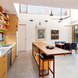 This is an example of a mid-sized contemporary galley open plan kitchen in Melbourne with a drop-in sink, flat-panel cabinets, light wood cabinets, solid surface benchtops, green splashback, ceramic splashback, stainless steel appliances, concrete floors and an island.