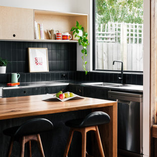 Inspiration for a contemporary l-shaped kitchen in Melbourne with an integrated sink, flat-panel cabinets, black cabinets, stainless steel benchtops, black splashback, stainless steel appliances, with island and grey benchtop.