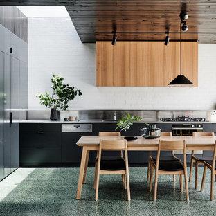 Cette photo montre une grande cuisine ouverte linéaire tendance avec un évier 2 bacs, un placard à porte plane, des portes de placard noires, un plan de travail en inox, une crédence en brique, un électroménager en acier inoxydable, béton au sol, aucun îlot et un sol vert.