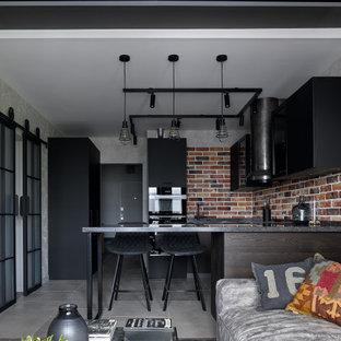 На фото: п-образная кухня-гостиная среднего размера в стиле лофт с плоскими фасадами, черными фасадами, коричневым фартуком, фартуком из кирпича, черной техникой, полуостровом, серым полом и черной столешницей