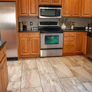 他の地域のトラディショナルスタイルのおしゃれなキッチン (中間色木目調キャビネット、ラミネートカウンター、シルバーの調理設備の、磁器タイルの床、アイランドなし、ベージュの床、緑のキッチンカウンター) の写真