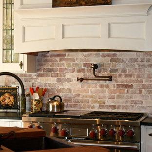 Inredning av ett lantligt mellanstort, avskilt kök, med en rustik diskho, skåp i shakerstil, vita skåp, träbänkskiva, rött stänkskydd, stänkskydd i tegel, rostfria vitvaror och en köksö