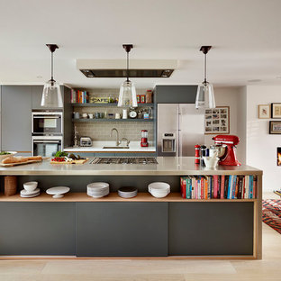 Photo of a large contemporary galley open plan kitchen in London with flat-panel cabinets, grey cabinets, stainless steel worktops, ceramic splashback, stainless steel appliances, light hardwood flooring, an island, beige floors, a submerged sink, grey splashback and grey worktops.