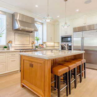 Traditional kitchen inspiration - Elegant u-shaped light wood floor kitchen photo in San Francisco with raised-panel cabinets, white cabinets, beige backsplash, stainless steel appliances and an island