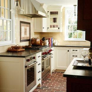 フィラデルフィアの中くらいのカントリー風おしゃれなキッチン (エプロンフロントシンク、シェーカースタイル扉のキャビネット、白いキャビネット、珪岩カウンター、ベージュキッチンパネル、セラミックタイルのキッチンパネル、シルバーの調理設備、レンガの床、赤い床、グレーのキッチンカウンター) の写真
