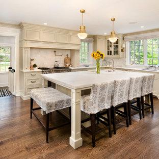 Klassische Wohnküche in L-Form mit Unterbauwaschbecken, Schrankfronten im Shaker-Stil, beigen Schränken, Küchenrückwand in Weiß, Kücheninsel, braunem Boden, weißer Arbeitsplatte, Marmor-Arbeitsplatte, Rückwand aus Marmor und braunem Holzboden in Philadelphia