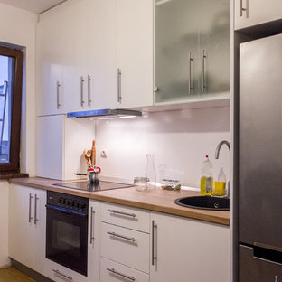 This is an example of a small contemporary single-wall enclosed kitchen in Other with a single-bowl sink, flat-panel cabinets, white cabinets, laminate countertops, white splashback, plywood flooring and no island.