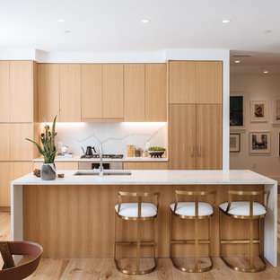 This is an example of a contemporary galley open plan kitchen in DC Metro with an integrated sink, flat-panel cabinets, medium wood cabinets, marble benchtops, white splashback, marble splashback, medium hardwood floors, with island and brown floor.
