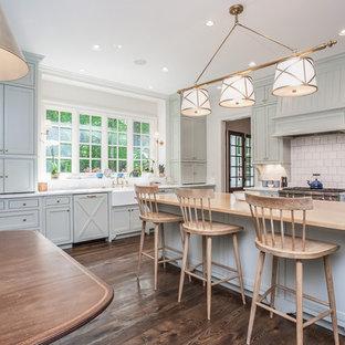Пример оригинального дизайна: большая п-образная кухня в стиле кантри с обеденным столом, раковиной в стиле кантри, фасадами с декоративным кантом, серыми фасадами, мраморной столешницей, белым фартуком, фартуком из плитки кабанчик, островом и темным паркетным полом
