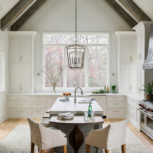 Coastal kitchen ideas - Example of a beach style medium tone wood floor kitchen design in Atlanta with recessed-panel cabinets, white cabinets, window backsplash, stainless steel appliances and an island