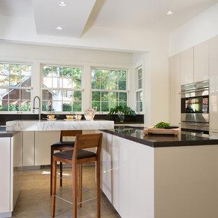 アトランタの巨大なコンテンポラリースタイルのおしゃれなキッチン (ダブルシンク、フラットパネル扉のキャビネット、ベージュのキャビネット、クオーツストーンカウンター、トラバーチンの床、シルバーの調理設備の) の写真