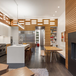 Design ideas for a mid-sized contemporary l-shaped open plan kitchen in Omaha with an undermount sink, louvered cabinets, medium wood cabinets, white splashback, stainless steel appliances, dark hardwood floors, with island, brown floor, white benchtop and quartz benchtops.