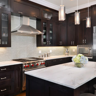 This is an example of a large transitional l-shaped kitchen in Chicago with shaker cabinets, dark wood cabinets, grey splashback, glass tile splashback, stainless steel appliances, an undermount sink, marble benchtops, medium hardwood floors and with island.