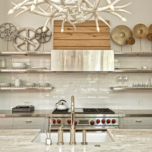 Contemporary kitchen in Chicago with open cabinets, stainless steel benchtops, white splashback, subway tile splashback and stainless steel appliances.