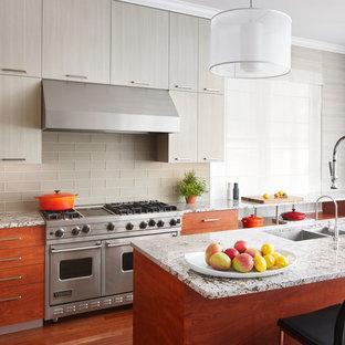 シカゴの広いモダンスタイルのおしゃれなキッチン (トリプルシンク、フラットパネル扉のキャビネット、グレーのキャビネット、御影石カウンター、グレーのキッチンパネル、ガラスタイルのキッチンパネル、シルバーの調理設備、無垢フローリング、茶色い床) の写真