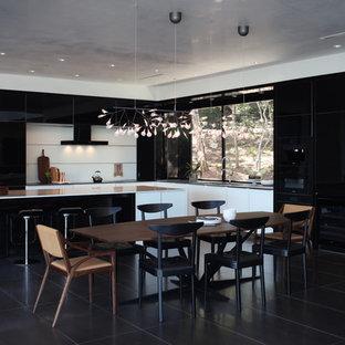 Idee per una cucina minimal con ante lisce, ante nere, paraspruzzi bianco, isola, pavimento nero, lavello sottopiano, top in marmo, paraspruzzi con lastra di vetro, elettrodomestici neri e pavimento in gres porcellanato