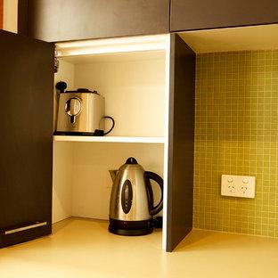 キャンベラの小さいモダンスタイルのおしゃれなキッチン (ダブルシンク、緑のキッチンパネル、ガラスタイルのキッチンパネル、シルバーの調理設備、無垢フローリング) の写真