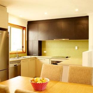 キャンベラの小さいモダンスタイルのおしゃれなキッチン (ダブルシンク、ラミネートカウンター、緑のキッチンパネル、ガラスタイルのキッチンパネル、シルバーの調理設備の、無垢フローリング) の写真
