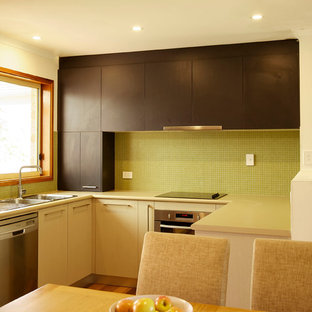 Inspiration for a small modern u-shaped eat-in kitchen in Canberra - Queanbeyan with a double-bowl sink, laminate benchtops, green splashback, glass tile splashback, stainless steel appliances and medium hardwood floors.