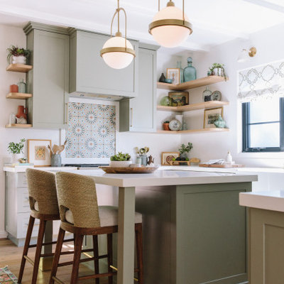 Example of a transitional u-shaped medium tone wood floor, brown floor and exposed beam kitchen design in Los Angeles with a farmhouse sink, shaker cabinets, green cabinets, quartz countertops, white backsplash, an island and white countertops