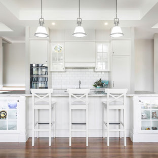 Inspiration for a transitional galley open plan kitchen in Brisbane with an undermount sink, shaker cabinets, white cabinets, white splashback, subway tile splashback, panelled appliances, dark hardwood floors, with island and white benchtop.