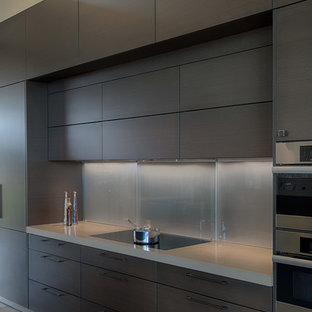 Idéer för ett mellanstort modernt kök, med en undermonterad diskho, släta luckor, skåp i mörkt trä, rostfria vitvaror, en köksö, bänkskiva i kvarts, grått stänkskydd, stänkskydd i glaskakel och mellanmörkt trägolv